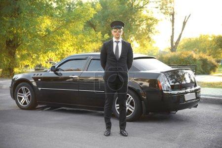 Photo pour Jeune chauffeur debout près de voiture de luxe dans la rue - image libre de droit
