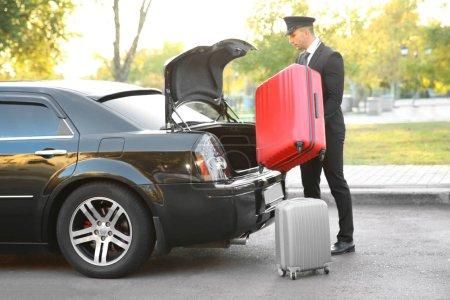Photo pour Chauffeur mettre une valise dans le coffre de la voiture - image libre de droit