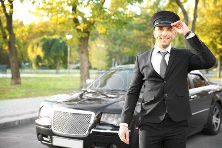 Photo pour Jeune chauffeur ajustant chapeau près de voiture de luxe dans la rue - image libre de droit