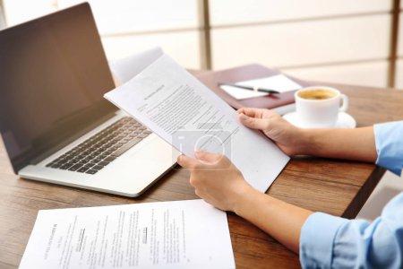 Photo pour Avocat assis à la table avec des papiers et un ordinateur portable - image libre de droit