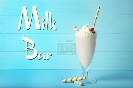 Glass of tasty milk shake on table. Text MILK BAR on background
