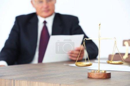 Photo pour Balance de justice sur table en bois et avocat masculin sur fond - image libre de droit