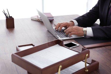 Photo pour Mâle avocate travaillant avec l'ordinateur portable au bureau, bouchent avec vue - image libre de droit
