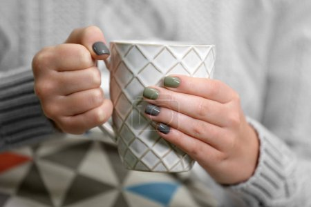 Female hands holding cup