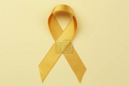 Photo pour Ruban d'or sur fond de couleur. Notion de cancer enfants - image libre de droit