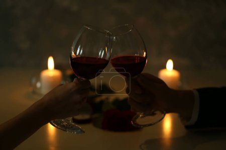 hands holding red wine glasses