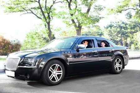 Photo pour Femme d'affaires en voiture avec chauffeur - image libre de droit