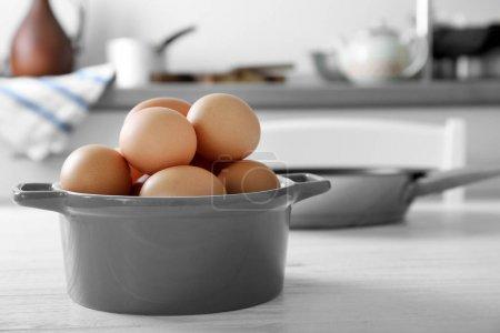 Raw eggs in saucepan