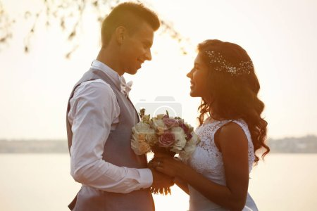Portrait of beautiful wedding couple outdoors on l...