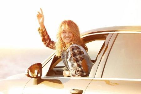 Photo pour Jeune conductrice en voiture sur la rive de la rivière - image libre de droit