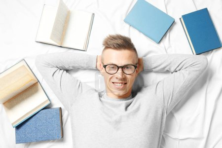 Photo pour Beau jeune homme allongé sur le lit des livres - image libre de droit