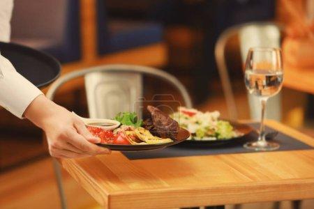Waiter serving meals in restaurant