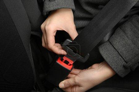 Woman fastening seat belt