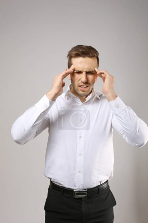 Young man suffering from headache on grey backgrou...
