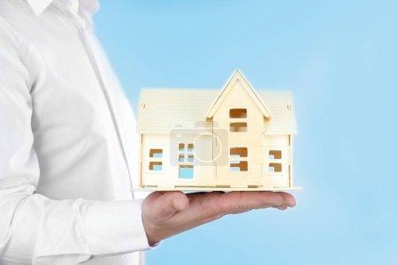 Man holding house model