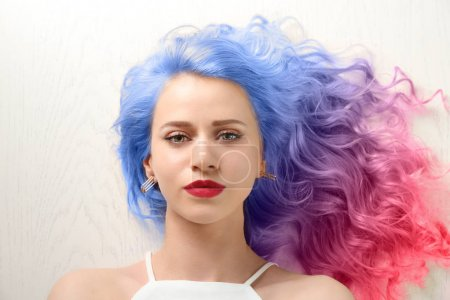 Photo pour Concept de coiffure tendance. Jeune femme avec des cheveux colorés teints sur fond blanc en bois - image libre de droit