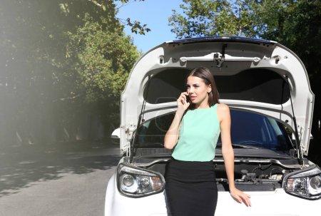 Businesswoman near broken car