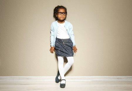 Photo pour Jolie petite afro-américaine contre un mur léger. Concept de mode - image libre de droit