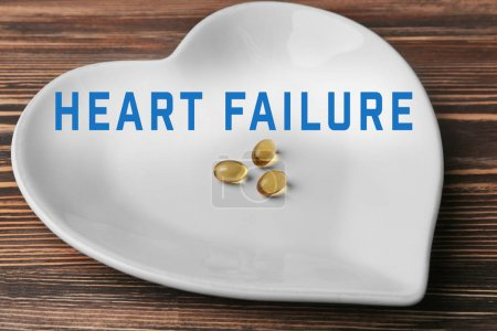 Photo for Cardiology and health care concept. Heart shaped plate with cod liver oil capsules on wooden table - Royalty Free Image