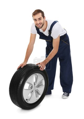 Photo for Young mechanic in uniform with wheel on white background - Royalty Free Image