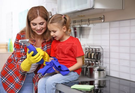 woman and daughter cleaning kitchen
