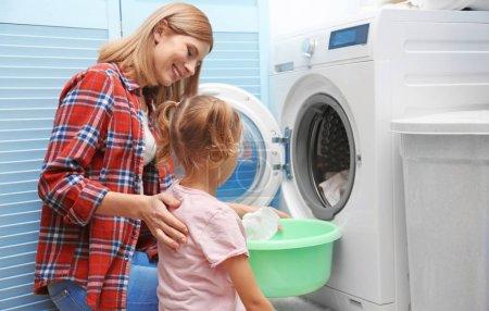Photo pour Jolie femme et sa fille faisant la lessive à la maison - image libre de droit