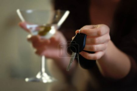 Woman with car key and glass of alcoholic beverage...