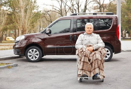 Man in wheelchair in front of car