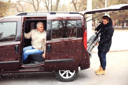 Young man loading wheelchair into car