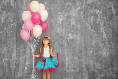 Photo pour Jolie fille d'anniversaire avec des ballons colorés près du mur de grunge - image libre de droit
