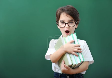 Photo for Cute little boy in glasses with books on green background - Royalty Free Image