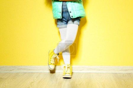 Photo pour Petite fille en denim contre un mur jaune. Concept de mode - image libre de droit