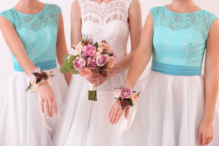 Bride holding wedding bouquet and bridesmaids