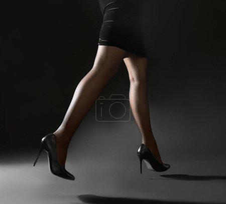 Beautiful woman legs in black tights on grey backg...