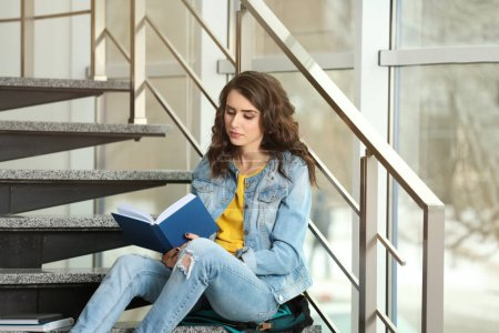 Beautiful young woman reading book while sitting on stairs near window