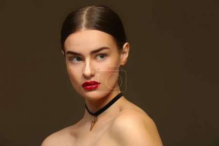 Portrait of beautiful young woman on color backgro...