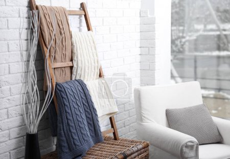 Knitted plaids hanging on ladder