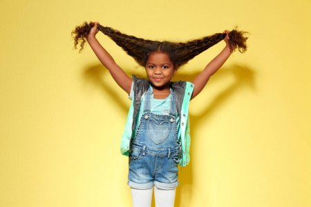 Photo for Cute little African American girl in denim against yellow wall. Fashion concept - Royalty Free Image