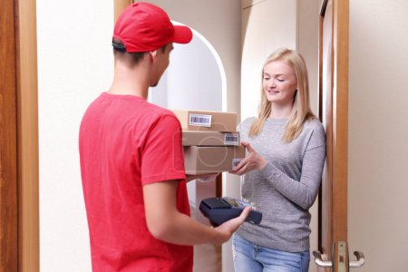 Young woman receiving package from courier