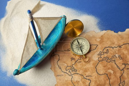Wooden boat, compass and old map