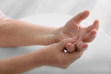 Elderly woman suffering from pain in hand