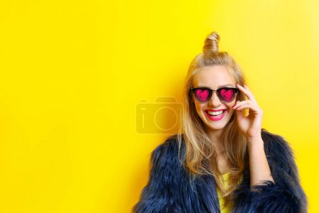Photo for Young beautiful woman wearing sunglasses with hearts on yellow background - Royalty Free Image