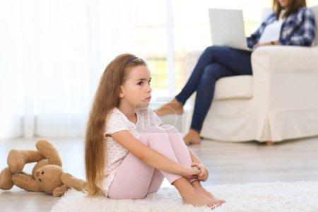 Sad little girl sitting on floor in room
