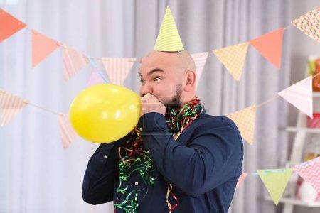 Funny fat man inflating balloon at birthday party