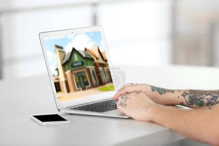 Online shopping concept. Man looking for house on real estate market website