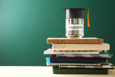 Photo for School supplies and glass jar with money for education on wooden table against green background - Royalty Free Image