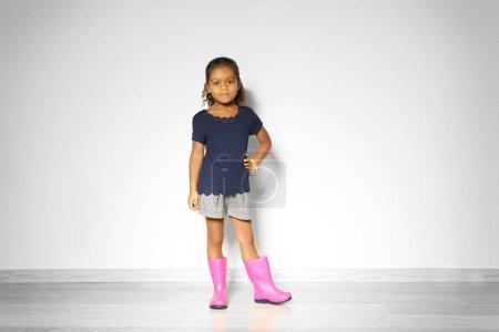 Photo pour Jolie petite afro-américaine en bottes en caoutchouc contre un mur léger. Concept de mode - image libre de droit