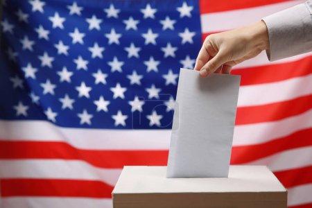 Hand inserting envelope in ballot box