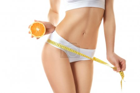 Woman with measuring tape and sliced orange