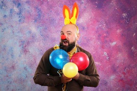 Photo pour Homme gras drôle avec décor de fête, ballons et oreilles de lapin sur fond de couleur - image libre de droit
